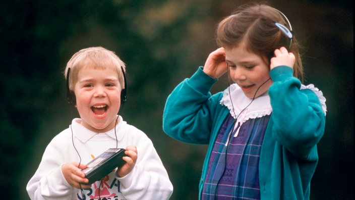 Vergnügt hören diese beiden Kinder zusammen Musik mit einem Walkman